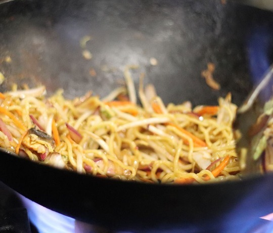 Wok filled with noodles and vegetables